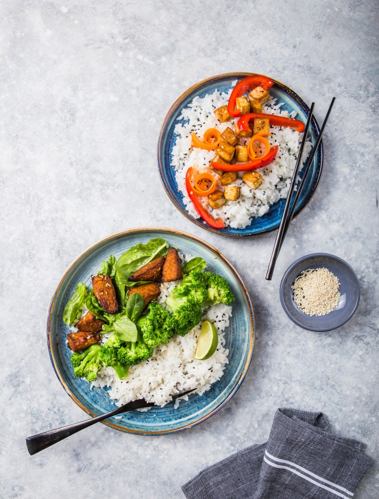 Two bowls of healthy vegan food including steamed rice and broccoli